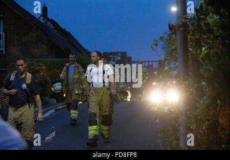 Siegburg, Germany. 08th Aug, 2018. Firefighters walk next to burnt-out houses after the fire on an embankment of the ICE line near Siegburg. Numerous people were injured in the fire. Credit: Thomas Frey/dpa/Alamy Live News - Stock Photo