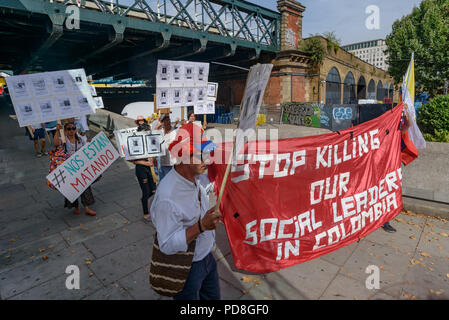 London, UK. 7th August 2018. Colombians and supporters of human rights walk with banners and Colombian flags and holding pictures of over a hundred murdered community leaders from the Southbank to Parliament Square in support of the peace process in Colombia and demanding an end to the daily threats and murders throughout the country. Credit: Peter Marshall/Alamy Live News - Stock Photo