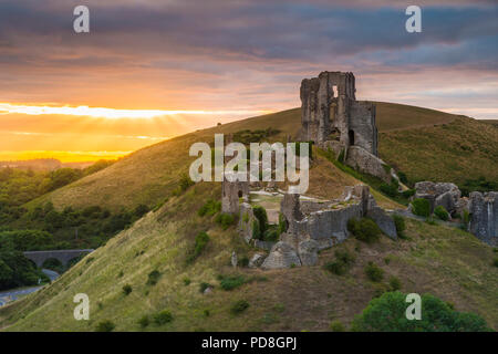 Corfe Castle, Dorset, UK.  8th August 2018.  UK Weather.  A dramatic sunrise at the ruins of Corfe Castle in Dorset.  The sunrise was soon obscured by a thickening band of cloud which produced light showers shortly after.  Picture Credit: Graham Hunt/Alamy Live News - Stock Photo