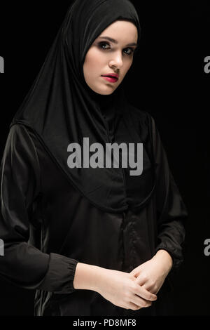 Portrait of beautiful young muslim woman wearing black hijab as conservative fashion concept on black background - Stock Photo