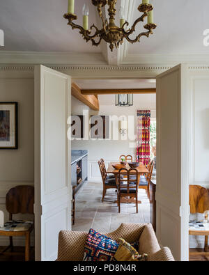 View through double doorway to vintage dining table and chairs - Stock Photo
