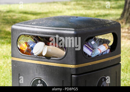 Rubbish Bin Overflowing with Unrecycled Plastic and Cardboard Waste in a Town Centre UK. - Stock Photo