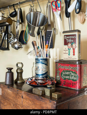 Brass weights and vintage sweet tins sit on an old oak box. Above various kitchen utensils hang from a wall rack - Stock Photo