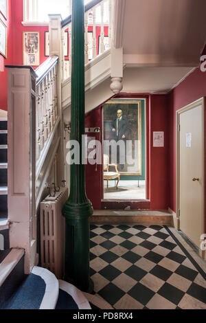 Entrance hall of the London Sketch Club with chequered flooring and red painted walls - Stock Photo