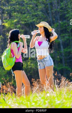 Two good pretty girlfriends in woodland - Stock Photo