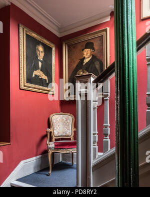 Framed portraits on red staircase wall of London Sketch Club - Stock Photo