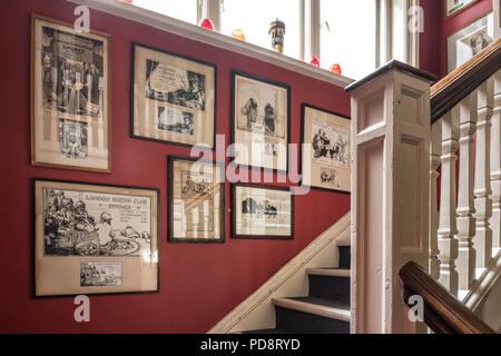 Old framed cartoons on the red staircase wall of the London Sketch Club - Stock Photo