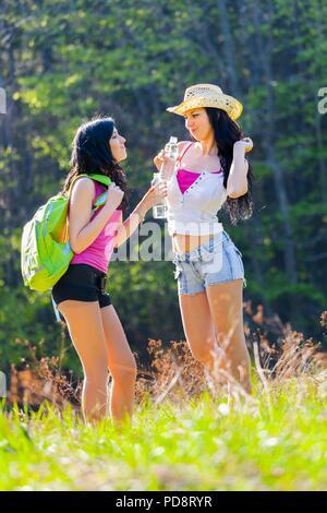 Two good pretty girlfriends in woodland candid shot fun - Stock Photo