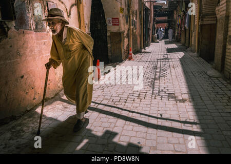 Marrakesh, Morocco - July 25th 2018 : an old man walking in the streets of old medina - Stock Photo