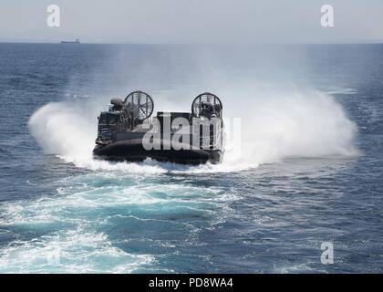 180703-N-XK809-118 PACIFIC OCEAN, (July 3, 2018) Landing craft air cushion (LCAC) 58, assigned to Assault Craft Unit (ACU) 5, approaches the well deck of the amphibious assault ship USS Bonhomme Richard (LHD 6), July 3, 2018. Bonhomme Richard is currently underway in the U.S. 3rd Fleet area of operations. (U.S. Navy photo by Mass Communication Specialist 3rd Class William Sykes). () - Stock Photo
