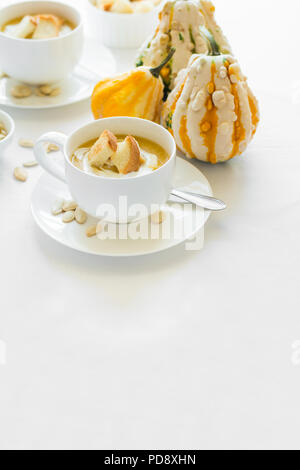 Two cups with fresh pumpkin cream soup decorated cream, seeds and crackers on white table cloth - Stock Photo