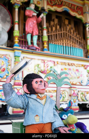 Mechanical monkey in front of a Steam Powered Victorian fairground organ at a steam fair in England. - Stock Photo