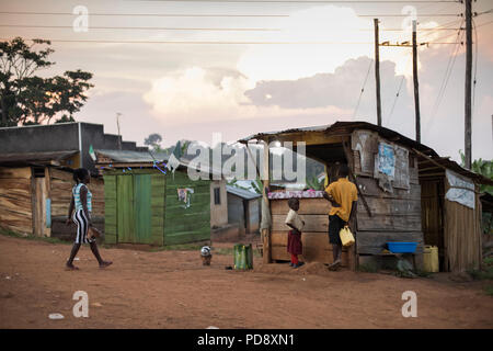 Shops and houses line the roadside of a small town in rural Mukono District, Uganda. - Stock Photo