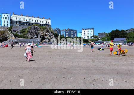 Tenby, Pembrokeshire, South Wales, UK. July 26, 2018.  Holidaymakers enjoying the Castle beach at low tide with lifeguards and castle to the right at  - Stock Photo