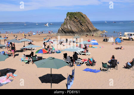 Tenby, Pembrokeshire, South Wales, UK. July 26, 2018.  Holidaymakers enjoying the North beach with the iconic Goscar rock on the shore at low tide in  - Stock Photo