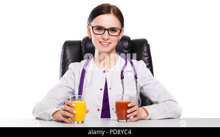 Female nutritionist sitting in her working place showing and offering glass of tomato and orange fresh juice on white background - Stock Photo