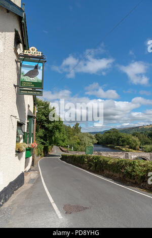 The Grouse Inn and an old stone arched bridge over The River Dee flowing through the Vale of Llangollen, Carrog, Denbighshire, North Wales, UK - Stock Photo