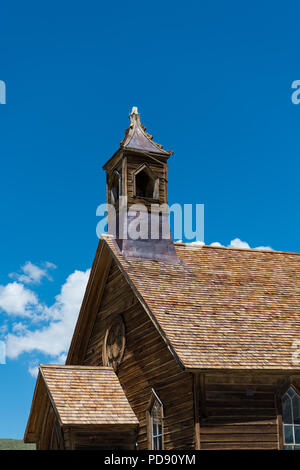 Abandoned old wooden church and steeple under beautiful blue sky and puffy clouds in the ghost town of Bodie, California - Stock Photo