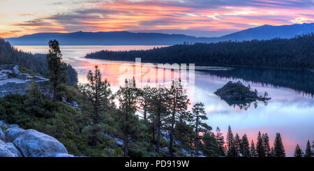 Panoramic view of a colorful sunrise over Emerald Bay and Eagle Point off Lake Tahoe in California. - Stock Photo