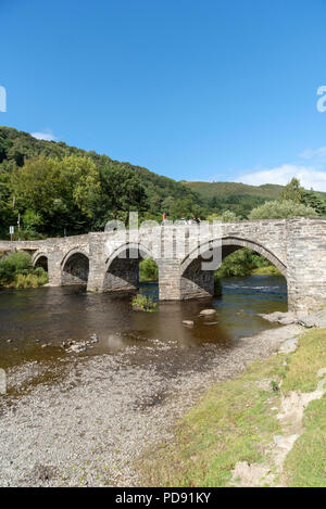 Old stone bridge crossing the River Dee at Carrog in the Llangollen Valley, Denbighshire, North Wales, UK - Stock Photo