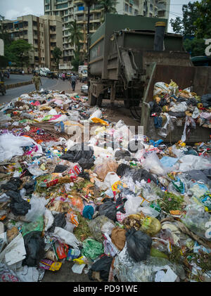 Plastic bags full of household rubbish lie on street next to dumpster in Mumbai, India