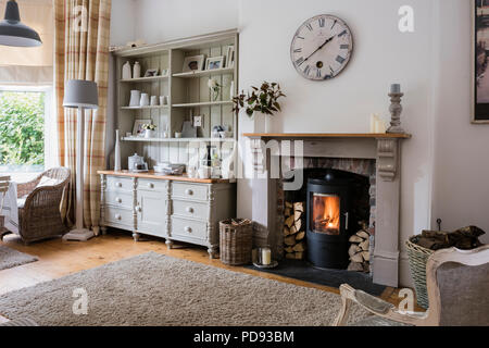 Large dresser in cosy open plan breakfast room with wall clock, woodburning stove and wicker chairs - Stock Photo