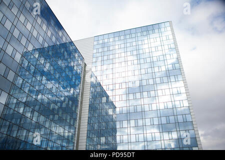 MAN Office building glass and steel with reflection of a perfect cloudy sky cbd downtown business district closing deals skyline - Stock Photo