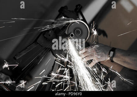 Angle grinder in use - Stock Photo