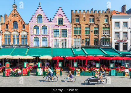 Three bicycles cycling past a line of restaurants in old styled traditional Flemish  buildings, Place de Bruges, Bruges, Belgium - Stock Photo