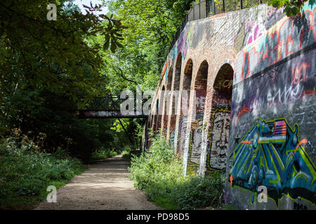 Colourful graffiti sprayed on disused railway bridges along the Parkland Walk, an old railway line and now London's longest Local Nature Reserve - Stock Photo
