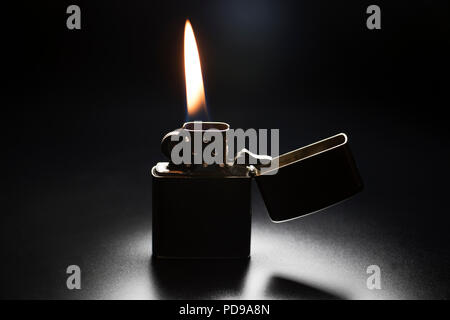 Zippo lighter with yellow flame isolated on black background. - Stock Photo