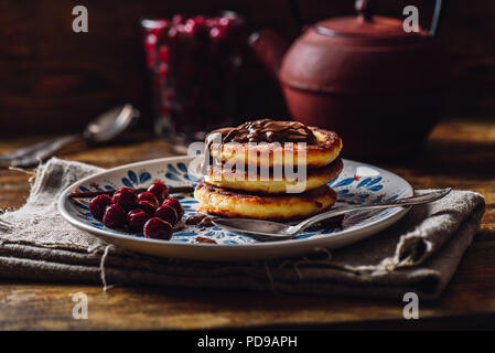 Breakfast with Quark Pancakes with Chocolate Paste and Frozen Cherry. Tea Pot with Spoons and Glass of Berries on Background. - Stock Photo