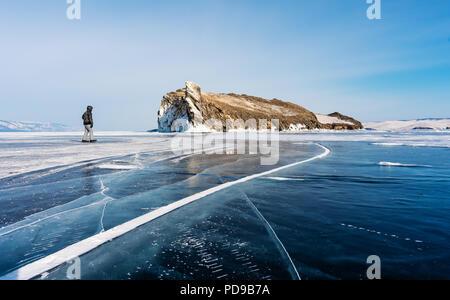 Travelling in winter, a man walking on frozen lake Baikal in Siberia, Russia - Stock Photo