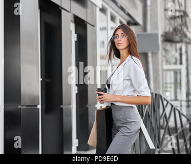 Side view of pretty model posing standing near shop, carrying bags and coffee. Beatiful girl wearing casual white shirt, grey classic trousers, transp - Stock Photo