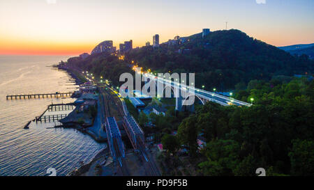 Drone view of the seaside with the railway, the illuminated Matsesta viaduct and mountains with dense forest at twilight, Sochi, Russia - Stock Photo