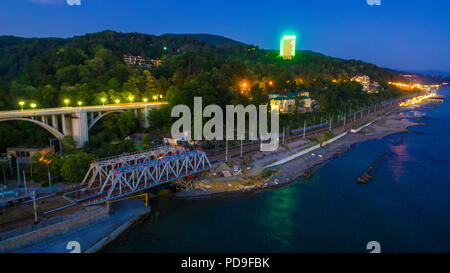 Drone view of the seaside with the Matsesta viaduct, the railway bridge and the mountain with dense forest at twilight, Sochi, Russia - Stock Photo