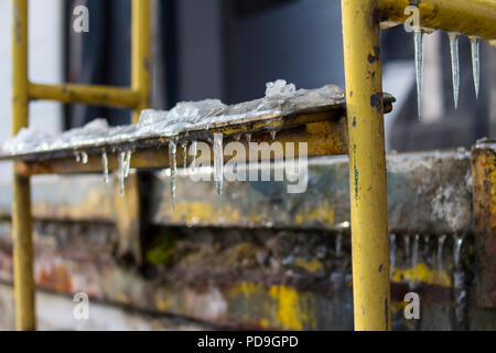 Ice and icicles on old rustic yellow stair steps outside slipping hazard risk - Stock Photo