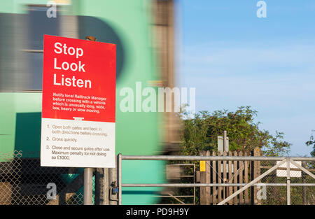 Unattended pedestrian railway train crossing with Stop, Look, Listen warning sign and a Southern train speeding past in West Sussex, England, UK. - Stock Photo