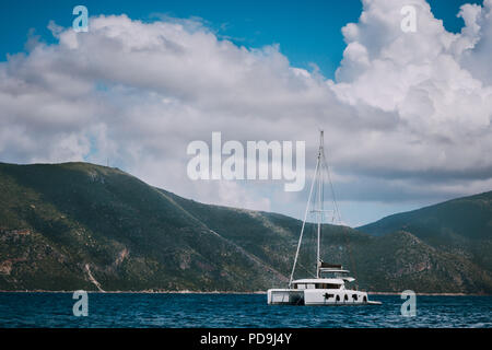 Catamaran ship in open sea near Fiskardo. Big clouds moving over the mountain shape of Ithaki island. Kefalonia Island Greece - Stock Photo
