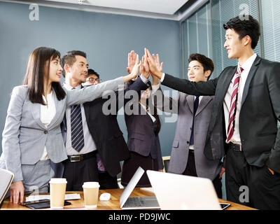 team of asian business people men and women putting hands together to show determination and unity. - Stock Photo