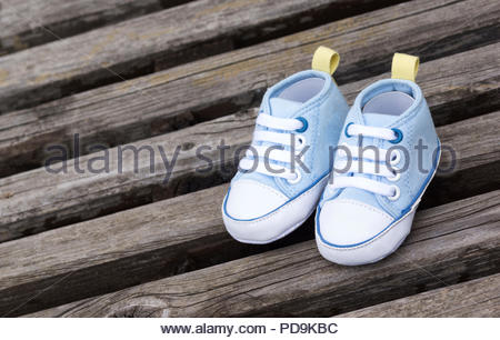 Blue baby shoes on a wooden surface - Stock Photo