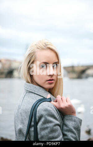 Fashionable blonde with long hair in a coat near Charles Bridge in Prague. Beautiful young woman outdoors. - Stock Photo