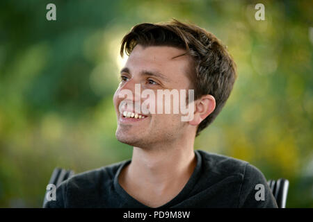 Young man, smiling, portrait, Germany - Stock Photo