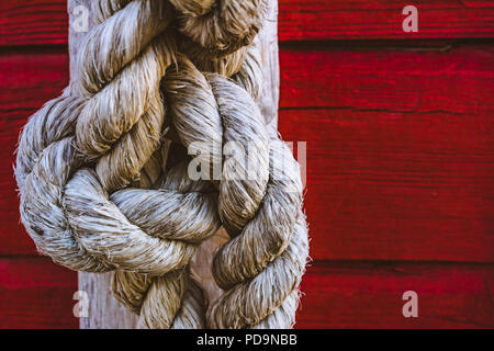rope knot on deep red wooden background - Stock Photo