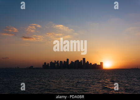 West Bay, downtown/CBD of Qatari capital Doha, from West Bay Lagoon, Persian Gulf, at sunset - Stock Photo
