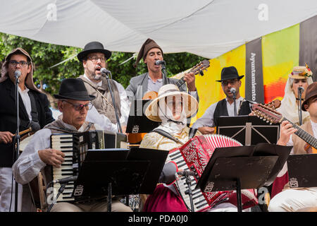 Folk musicians with accordians, timples and guitars, dressed in traditional costume playing on stage for the day of the Canaries, Alcala, Tenerife, Ca - Stock Photo