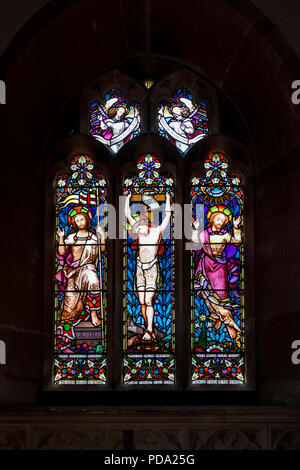 Traditional stained glass window in the chancel of the Parish church of St Michael in Little Bedwyn, a small rural village in Wiltshire, south England - Stock Photo