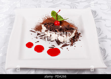 Tiramisu. Classical Dessert with cocoa and chocolate on white square plate. Garnished with Cherry and Mint. Sweet dessert in the restaurant. Morning light - Stock Photo