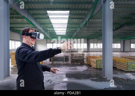 Construction worker at indoor construction site wearing vr eyeglasses or goggles and gesturing - Stock Photo