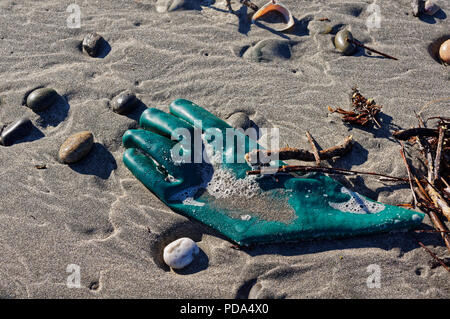 Green rubber glove washed up on a beach on New Zealand's west coast - Stock Photo